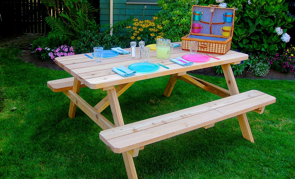 DIY picnic table with attached benches set for a meal.