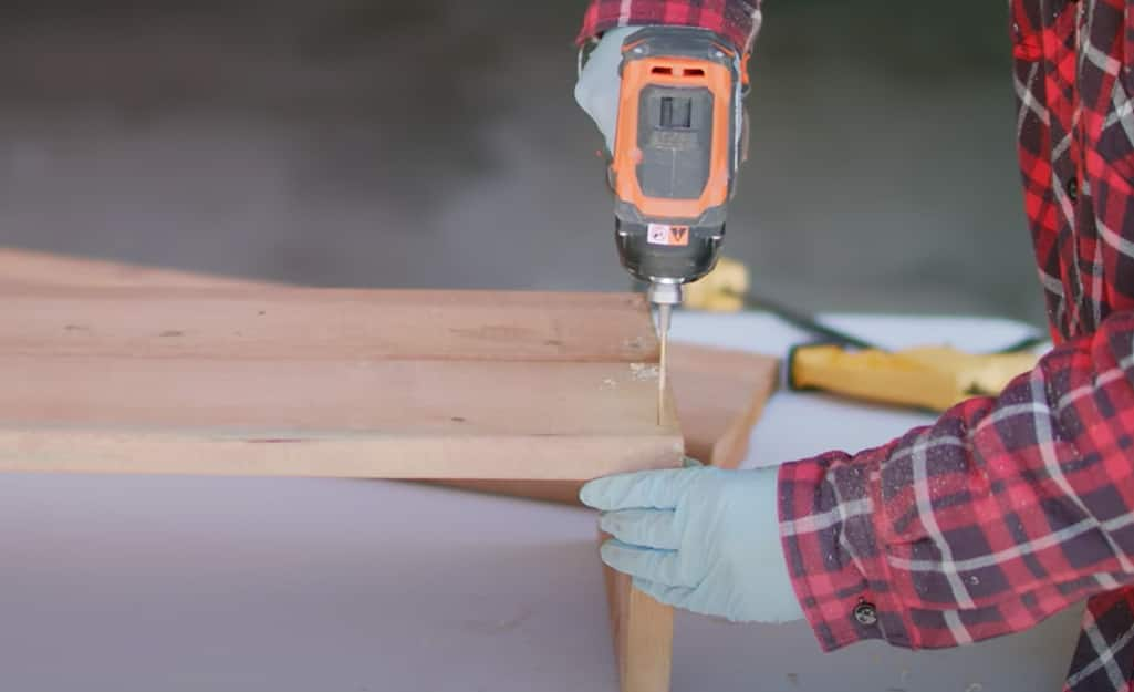 A person drilling into a wood board.
