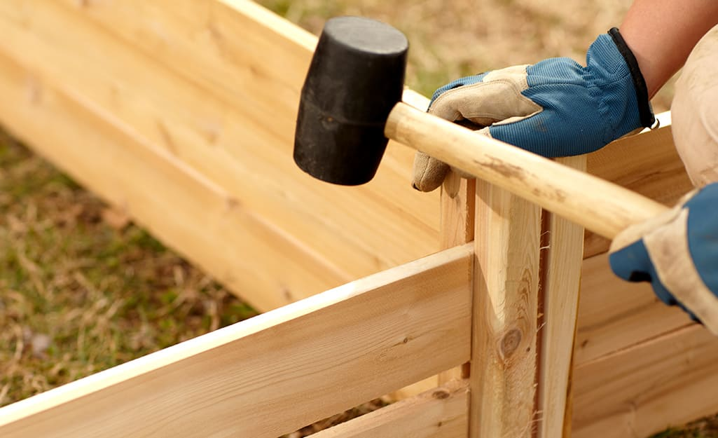 A person using a rubber mallet to build  a raised garden bed.