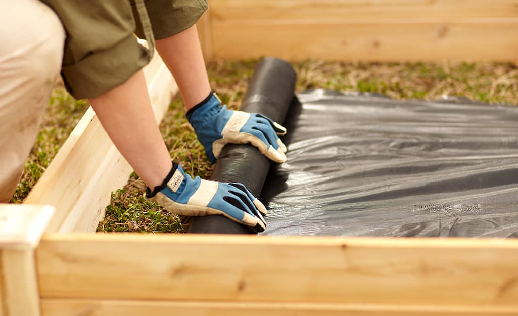 A person placing landscaping fabric in a raised garden bed.