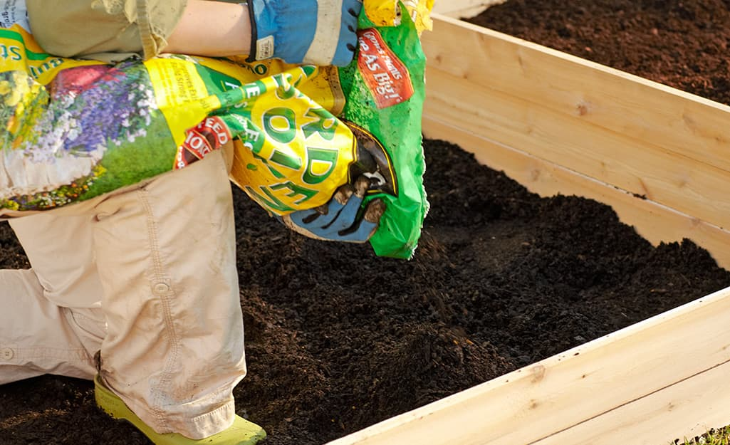 A person adding soil to a raised garden bed.