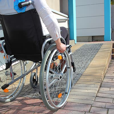 A person in a wheelchair using a ramp.