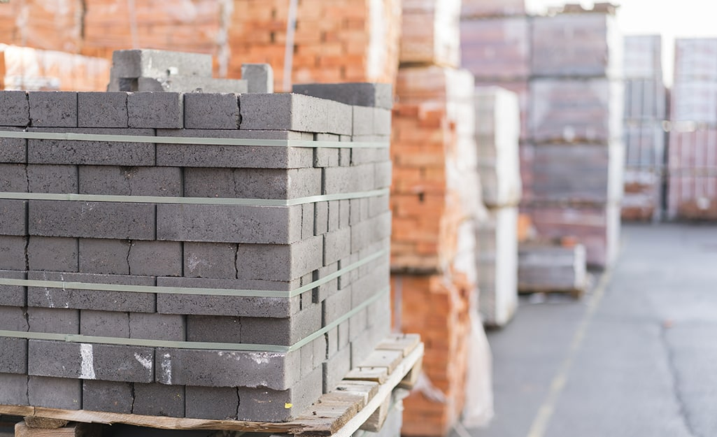 Pallets of paver stones and retaining wall blocks of different materials.