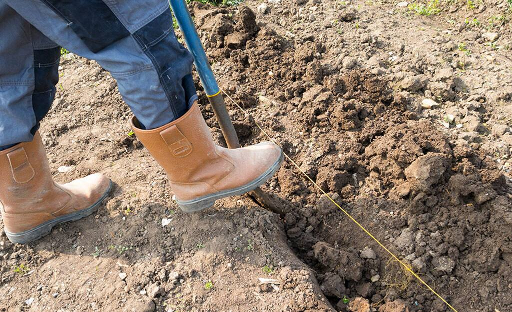 A person digging a trench with a shovel.