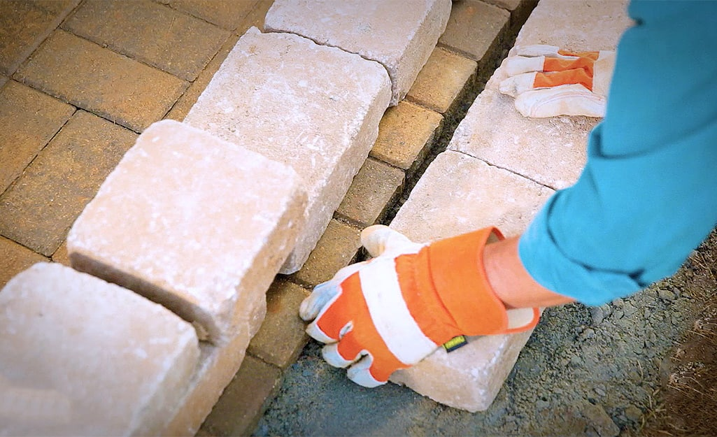 A person laying the first course of retaining wall blocks.