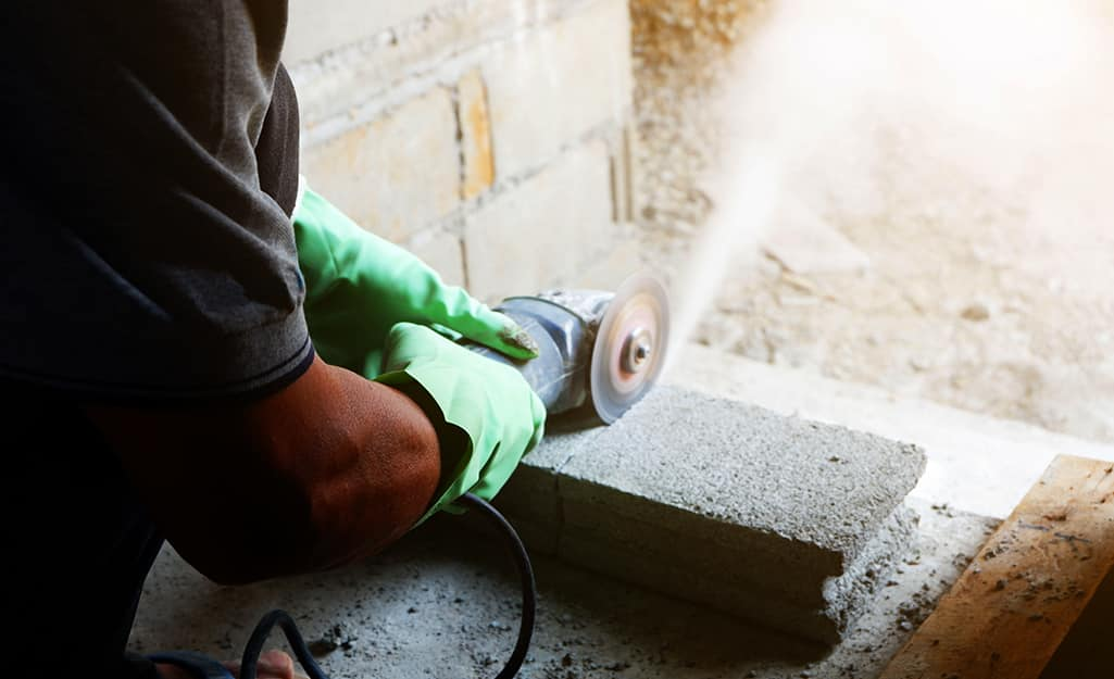A person cutting a cement block with a masonry saw.