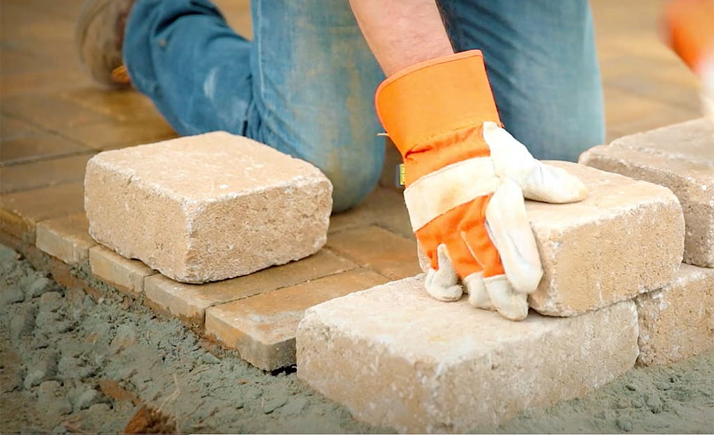 A person laying a second course of retaining wall blocks.