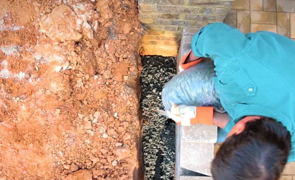 A man pouring gravel to backfill a retaining wall.