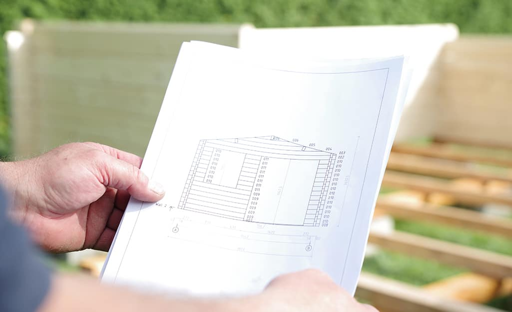 A person holds blueprints for how to build a shed.