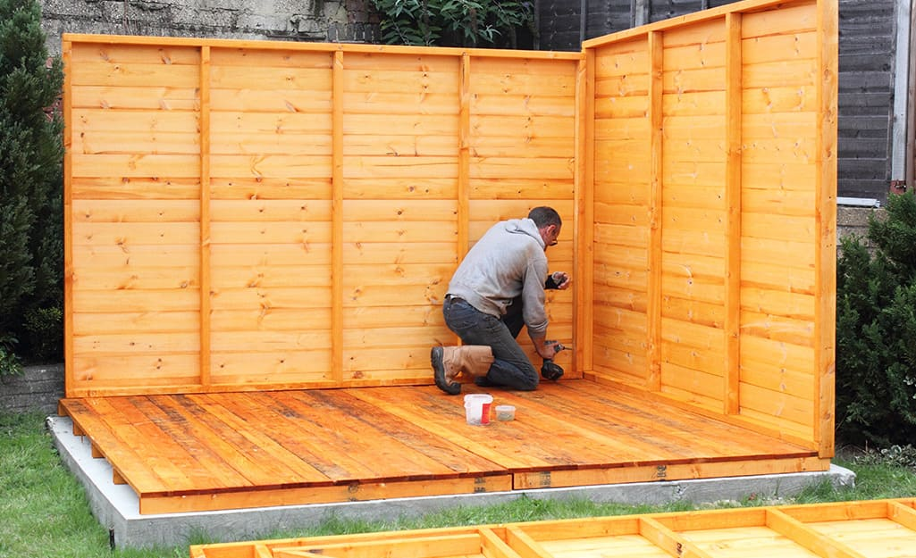 A man installs the back and side walls of a wood shed.