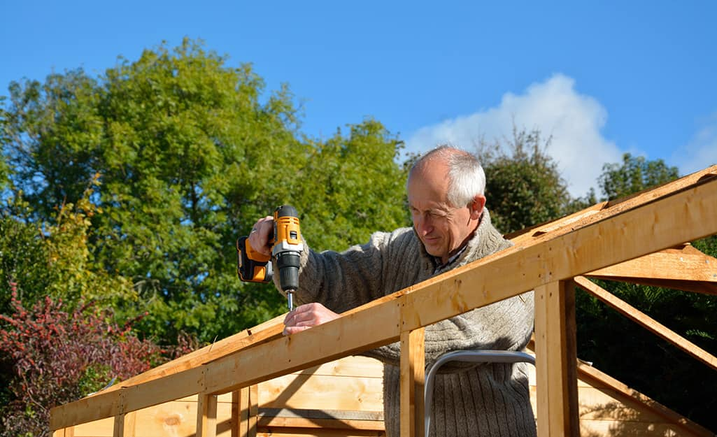 A man drilling into the post for the roof of a shed.