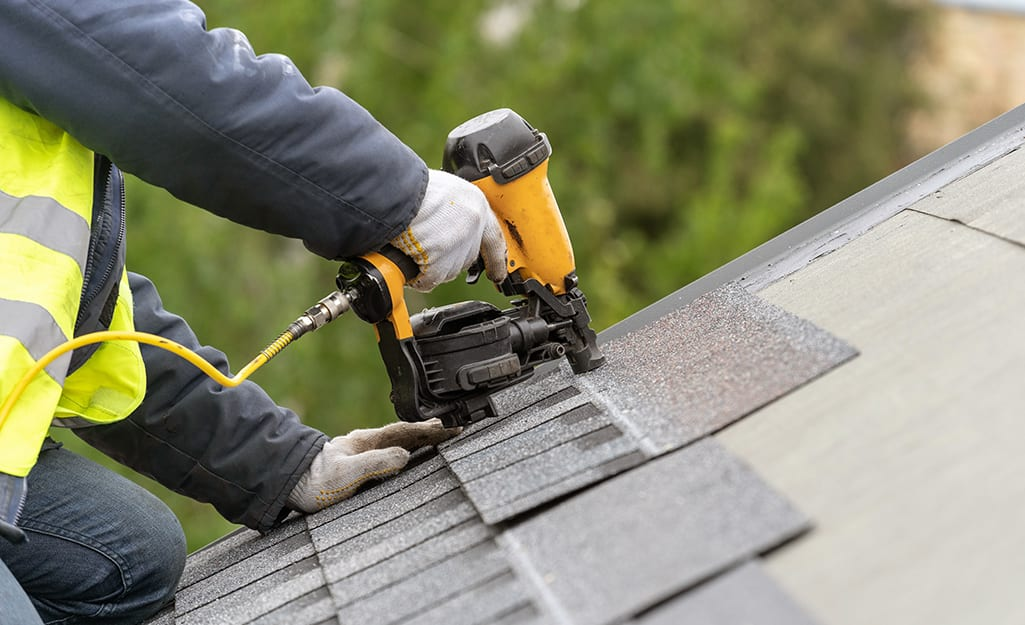 A man installing roof roofing shingles.