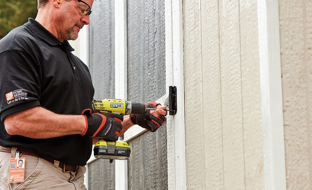 A person using a drill to install the door of a shed.