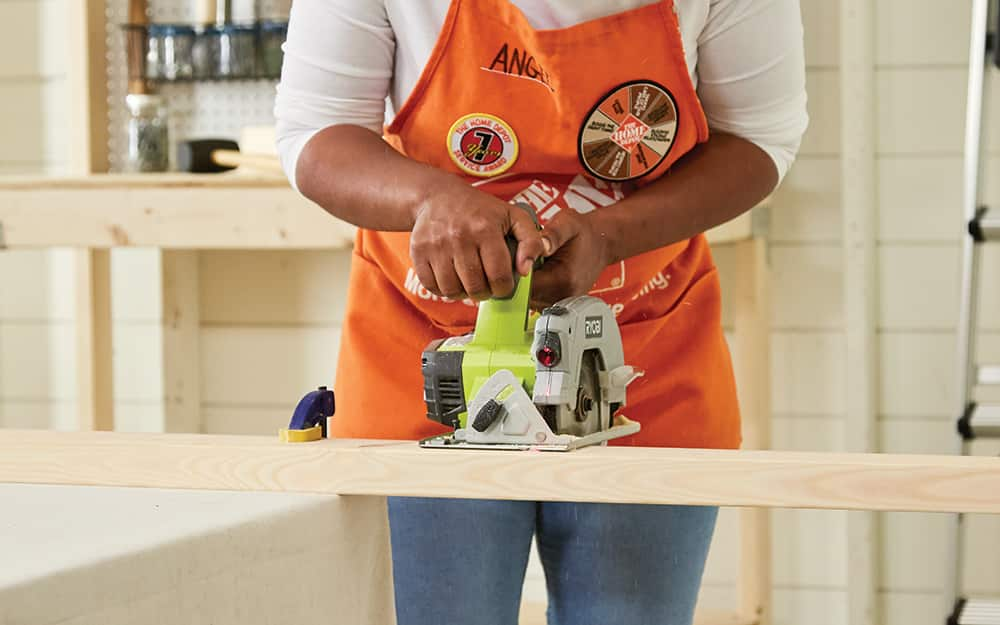 Woman uses circular saw to cut 2x4s for tote