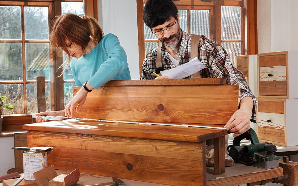 Two people measuring wood to build a staircase.