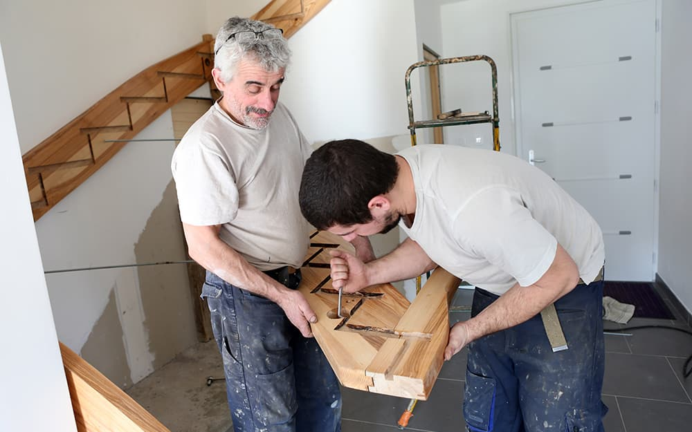 Two people carving out a hole in a staircase stringer.