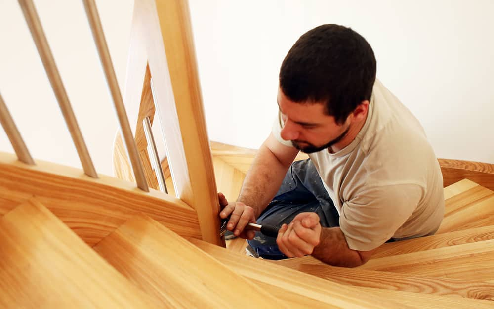 Someone securing the banister for handrail with wood screws.