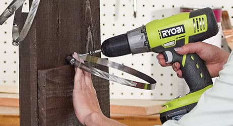Person drilling metal rings into a board