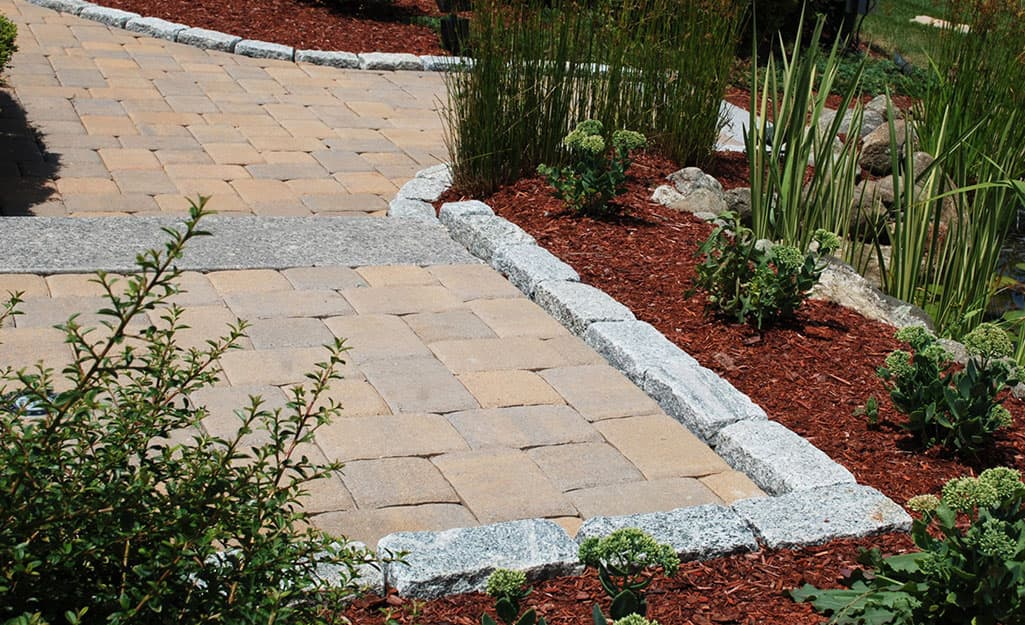A walkway edged with pavers beside a garden bed.