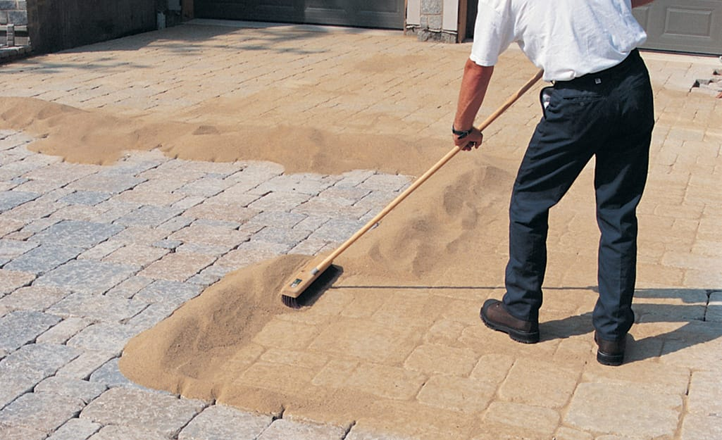 A man using a push broom to sweep sand over a paver walkway.