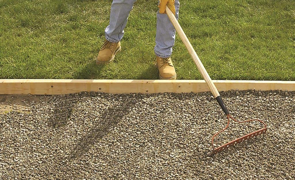 Someone using a landscape rake to level a bed of crushed gravel for a walkway.