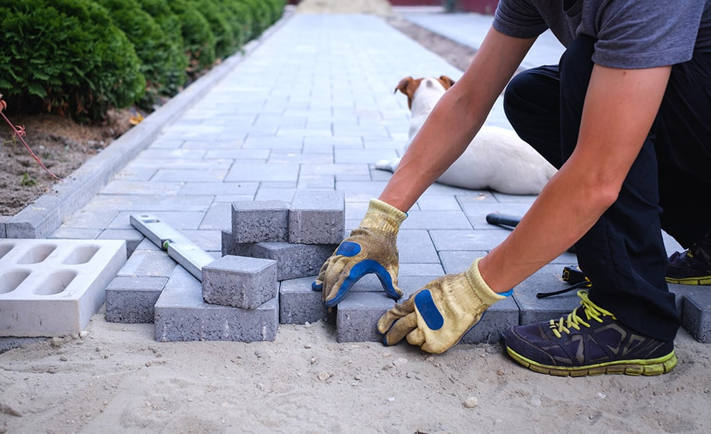 Someone wearing work gloves and laying pavers to build a walkway.