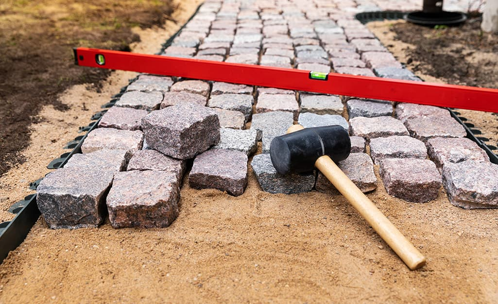 A mallet and level sitting on top of pavers being used to build a walkway.