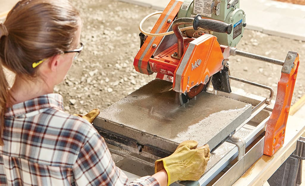 A woman in safety eyewear and work gloves using a concrete saw to cut pavers for a walkway.
