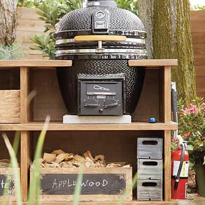 An outdoor grill station built around a komodo-style grill.