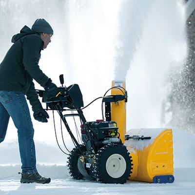 A man operating a yellow, walk-behind snow blower