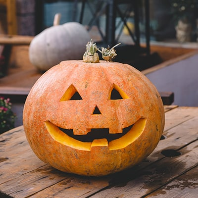 A freshly carved pumpkin sits on an outdoor table.