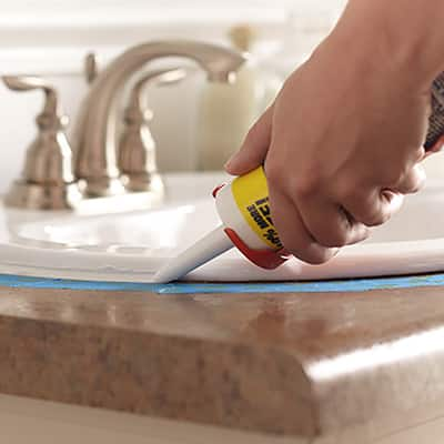 A person applying caulk around bathroom sink.