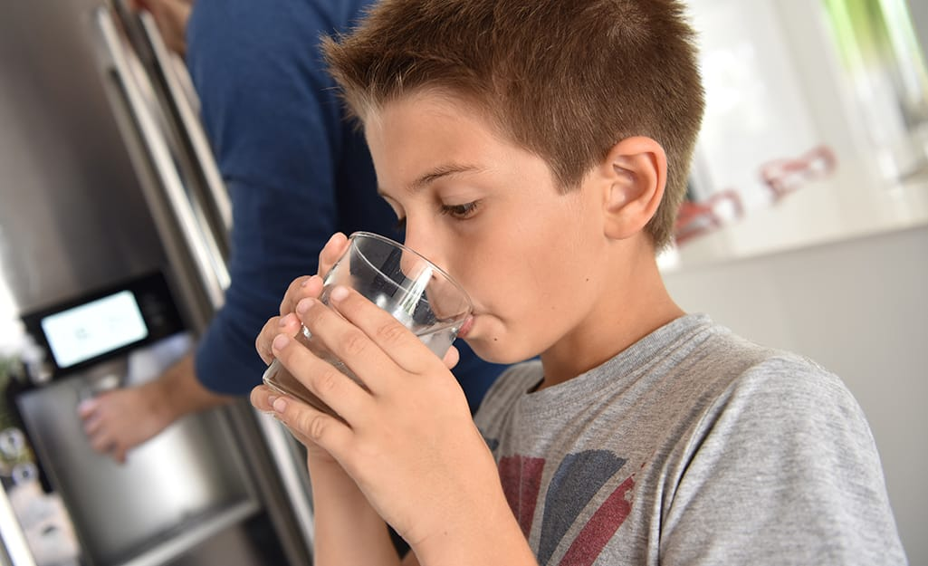 A kid drinking a glass of water from the fridge.