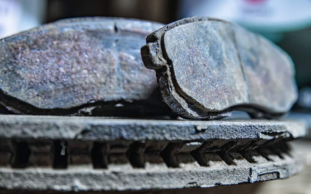 A close up of worn brake pads