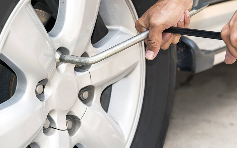 A person removing lug nuts from a tire plate