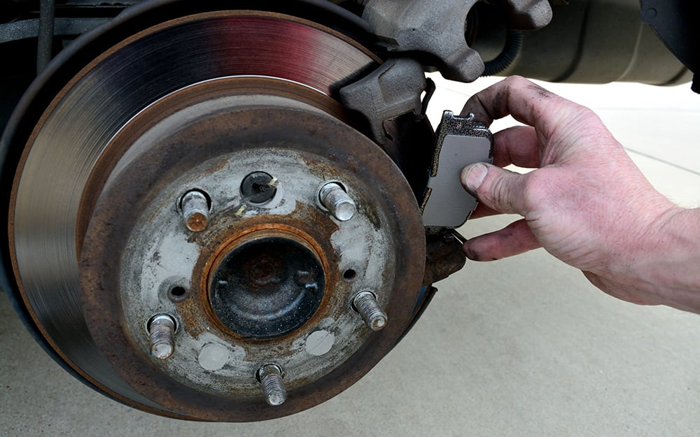 A person removing old brake pads