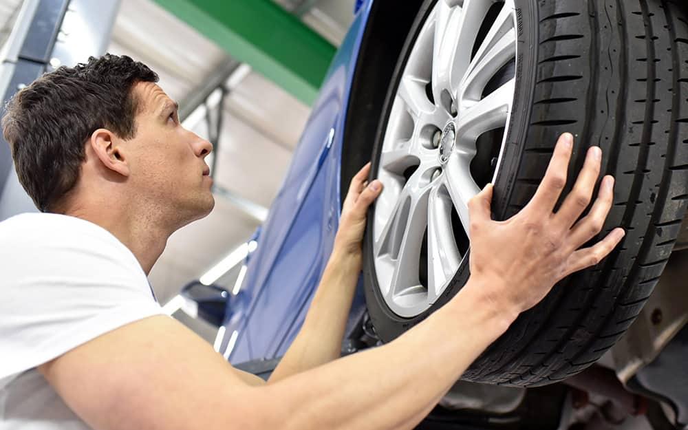 A man installing a tire on a car