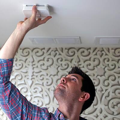 Man opening smoke alarm in ceiling.