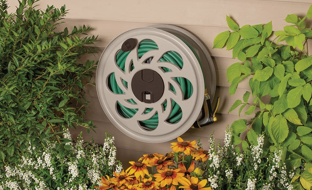 A garden hose is wound on a hose reel that's mounted on house siding.