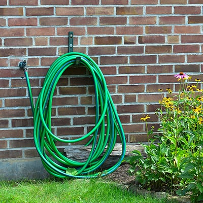 A garden hose is coiled up on a hose rack mounted on brick.