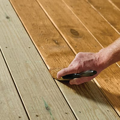 A person applies exterior wood stain to deck boards with a paint brush.