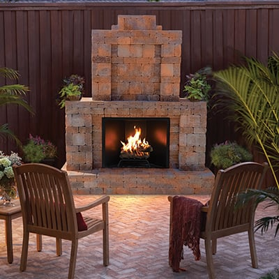 An outdoor fireplace on a patio with patio chairs.