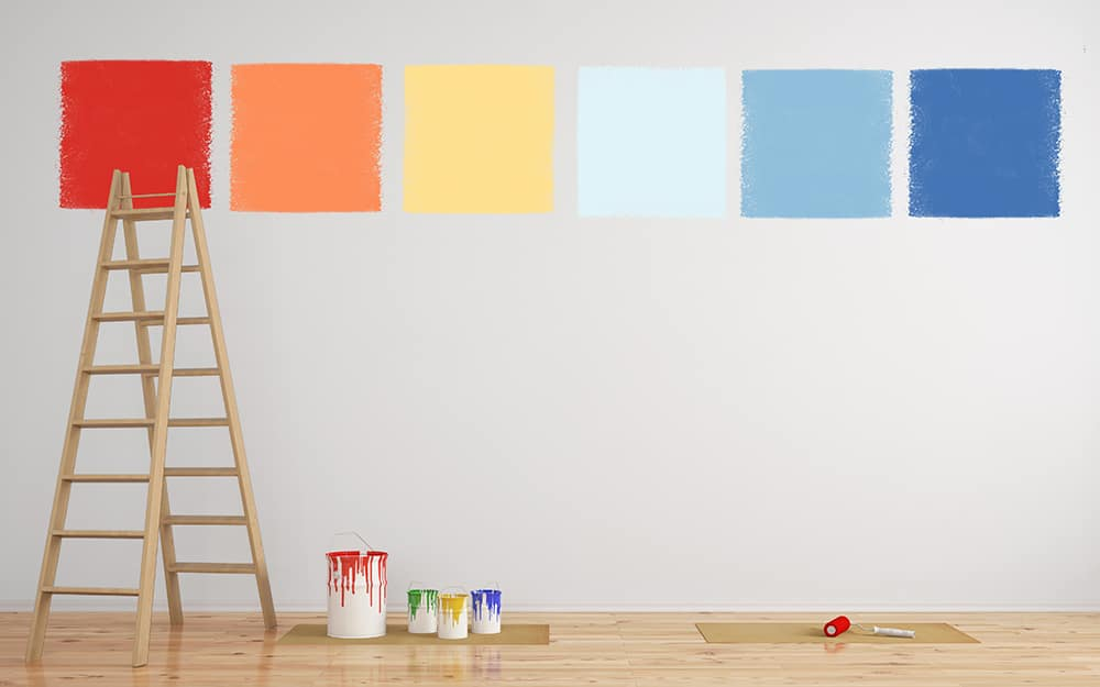 A ladder rests against a wall featuring large test paint squares of different colors.