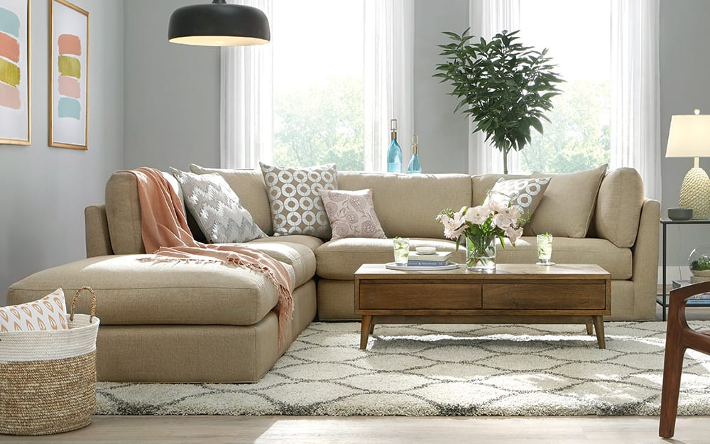 A living room with white sofa and pink throw pillows.