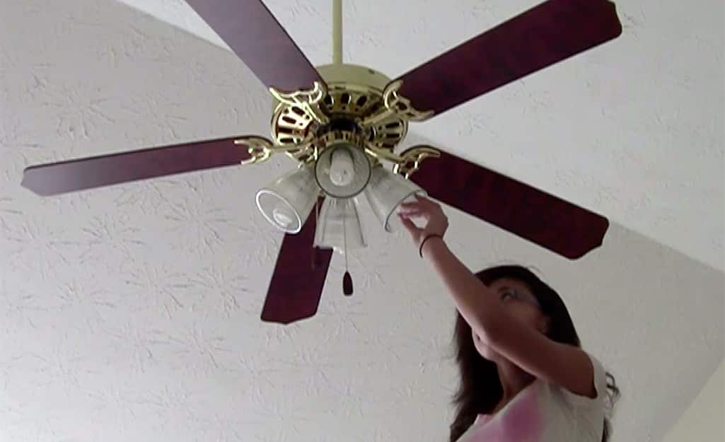 A person changing the light bulb on a ceiling fan.