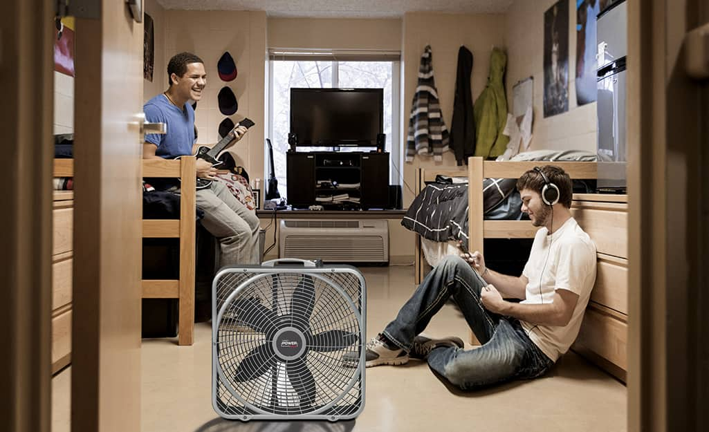 Two men in a room with a box fan.