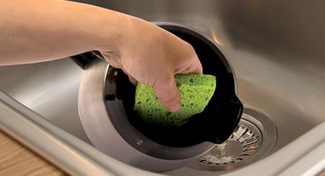 Someone cleaning the inside of a coffee pot with a sponge.