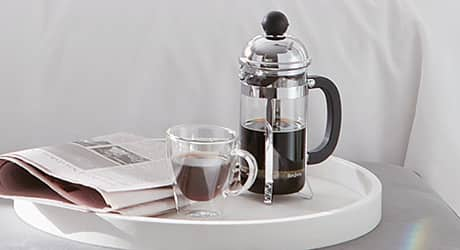 A French press coffee maker on a white tray.