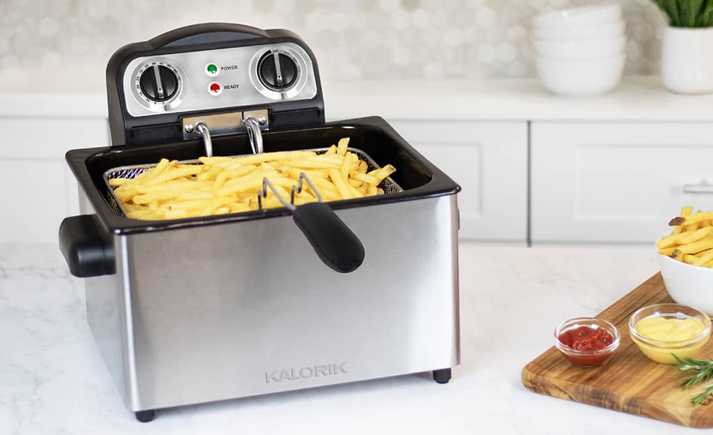 A deep fryer filled with food on a stove top