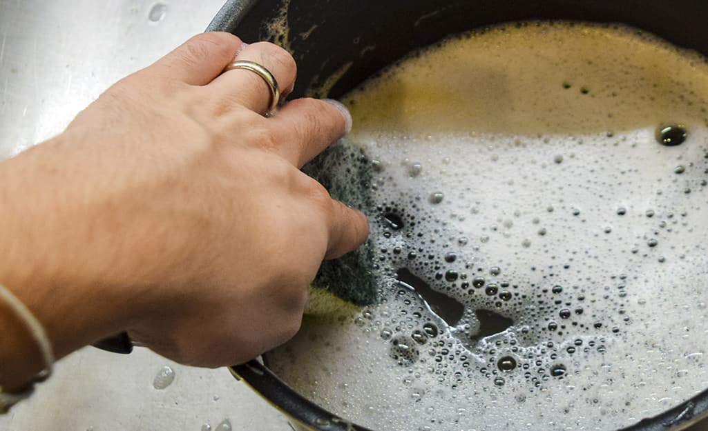 A close up of a hand scrubbing the inside of a deep fryer